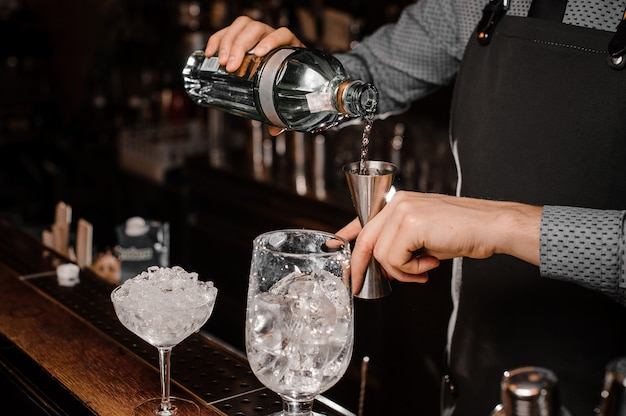 Barmans hands pouring alcoholic drink into a jigger to prepare a fresh cocktail