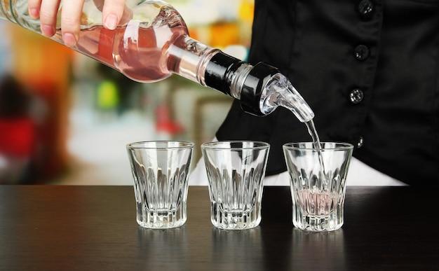 明るい背景で、グラスに飲み物を注ぐボトルとバーメンの手