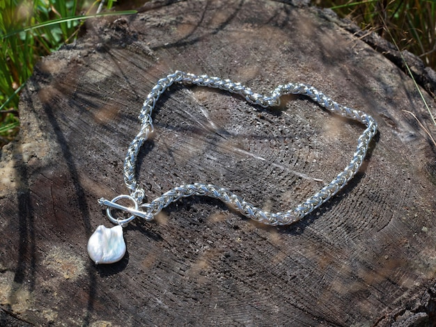 Baroque pearl pendant with silver chain on brown tree stump