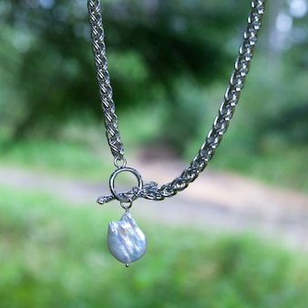 Baroque pearl pendant with silver chain on green nature background