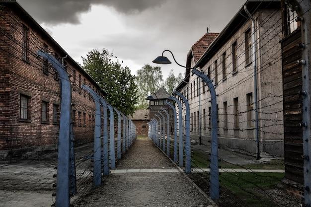 Казармы и забор из колючей проволоки, территория немецкой тюрьмы аушвиц ii, биркенау, польша.