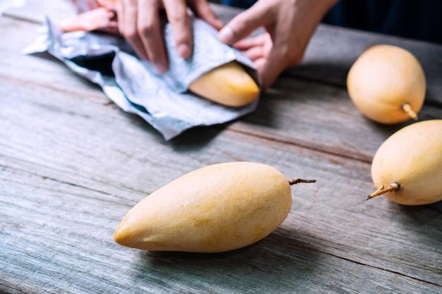 木製のテーブルにバラクーダマンゴー。甘くて美味しいタイの果物。閉じる