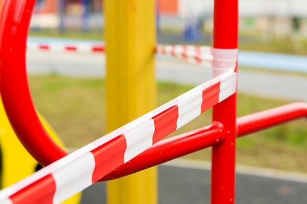 Заградительная лента на детской площадке. красно-белая полосатая лента. стоп линия