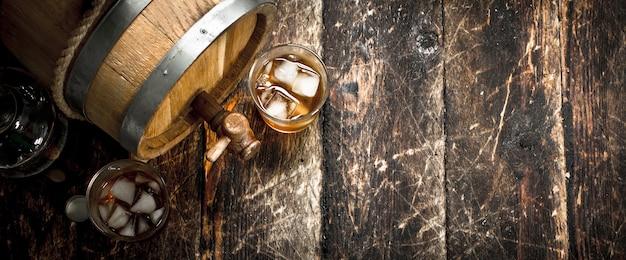 ガラスとスコッチウイスキーの樽。木製の背景に。