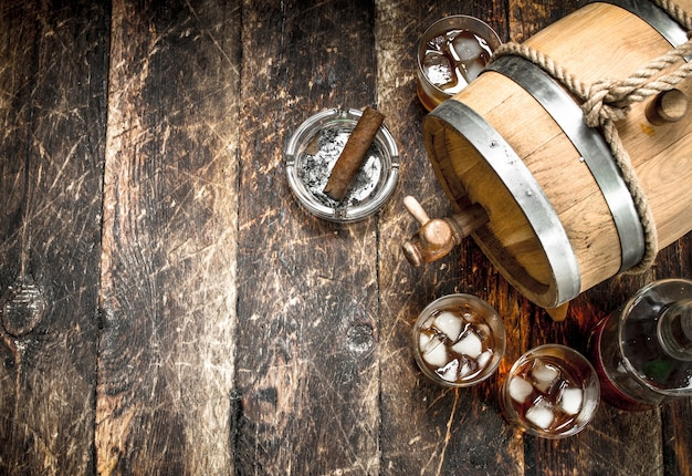 Barrel of scotch whiskey with a glass. on a wooden background.