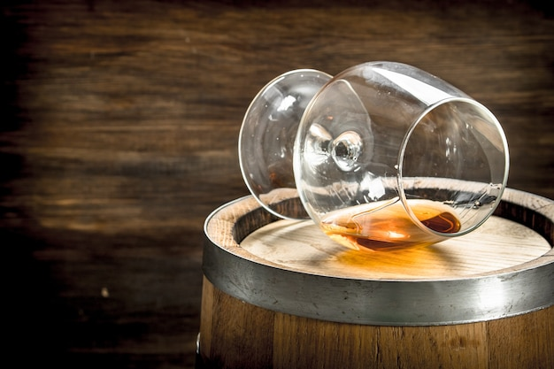 コニャックのガラスが付いているバレル。木製の背景に。