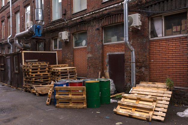 Barrels and pallets are in the yard of the warehouse