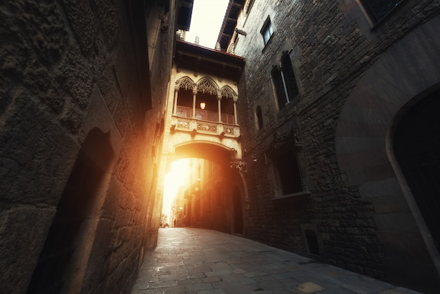 Barri gothic quarter and bridge of sighs during sunrise in barcelona, catalonia, spain.