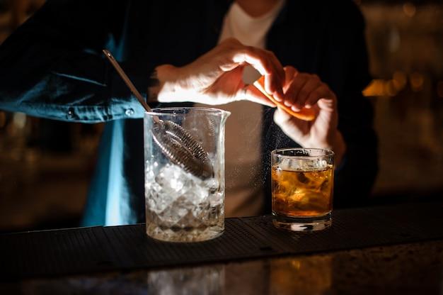 Баррман брызгает апельсиновой цедры в бокал для коктейля