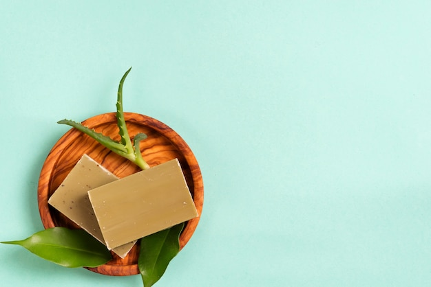 Bars of green natural olive oil soaps with green leaves and aloe vera in a plate on blue