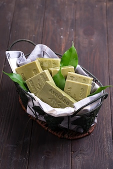 Bars of green natural olive oil soaps with green leaves in a basket on dark wooden