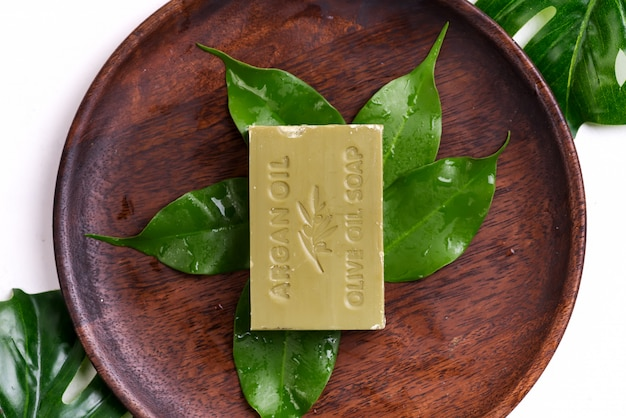 Bars of green natural olive oil soaps with green leaves on a wooden plate on white
