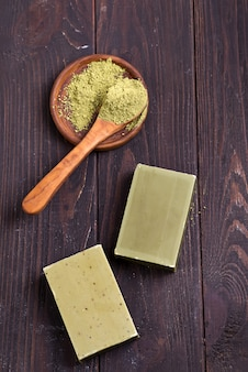 Bars of green natural olive oil soaps with green powder on dark wooden