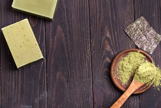 Bars of green natural olive oil soaps with green powder and dry seaweed on dark wooden