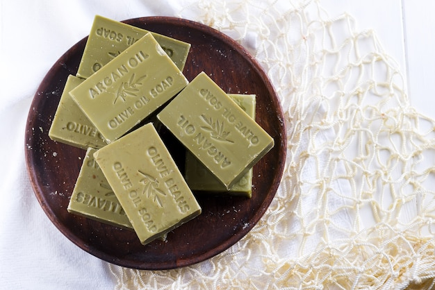 Bars of green natural olive oil soaps on a wooden plate on white