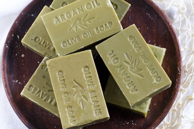 Bars of green natural olive oil soaps on a wooden plate