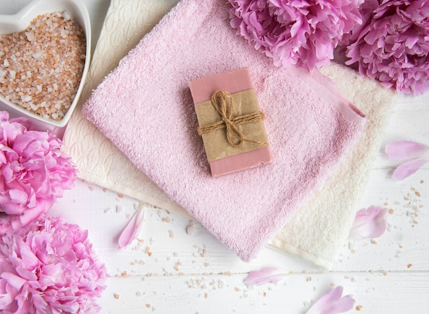Bars of handmade soap,  soft towels and peony flowers