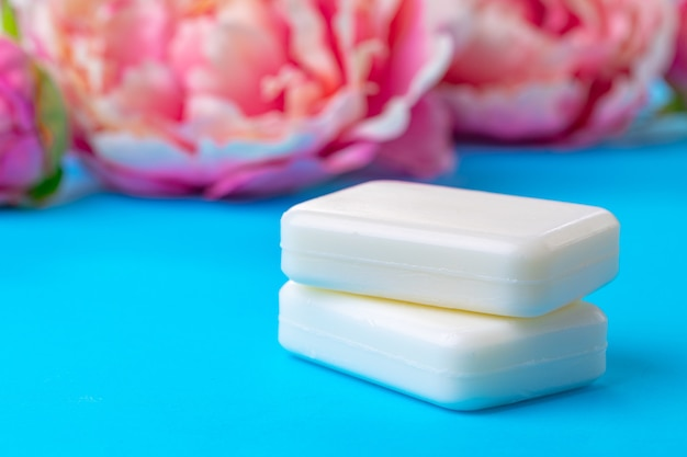 Bars of handmade soap with flowers on the table, close up