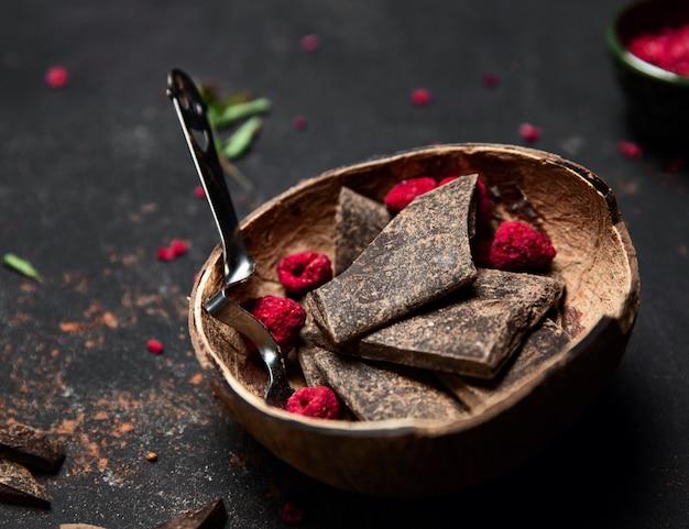 ココナッツプレートの装飾としてブラックチョコレートと昇華ラズベリーのバー。
