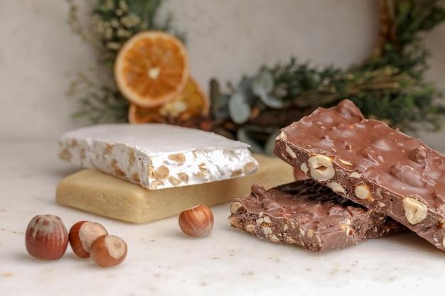 白いテーブルの上にクルミと甘いチョコレートヌガーのバー