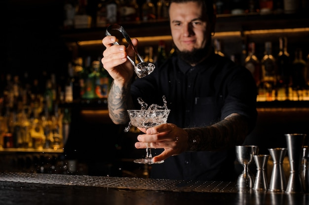 Bartender adding to an alcoholic drink in the glass a big ice cube with tweezers on the bar counter