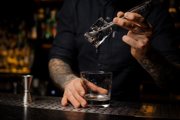 Bartender adding to a alcoholic drink in the glass a big ice cube with tweezers on the bar counter