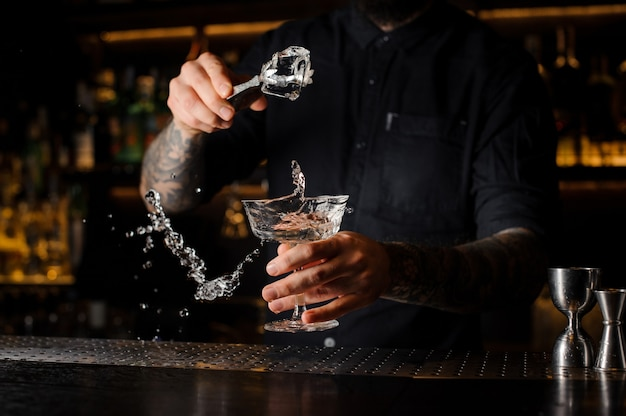 Bartender adding to an alcoholic drink in the glass an ice cube with tweezers on the bar counter