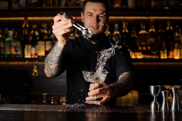 Bartender adding to an alcoholic drink in the glass an ice cube with tweezers with splash on the bar counter