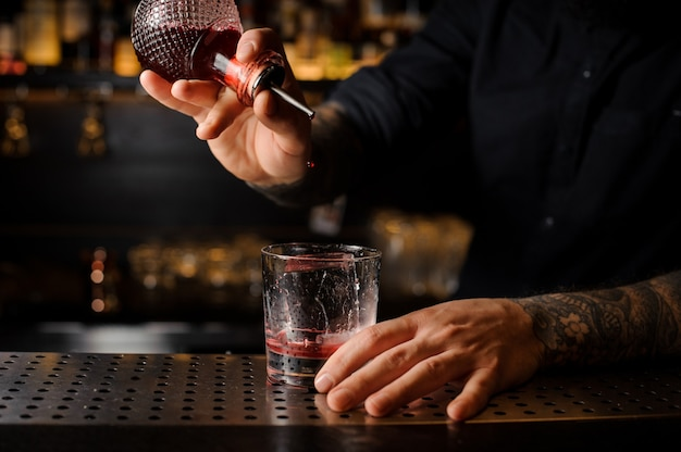 Bartender adding a bitter to the cocktail from the special dasher bottle on the bar counter