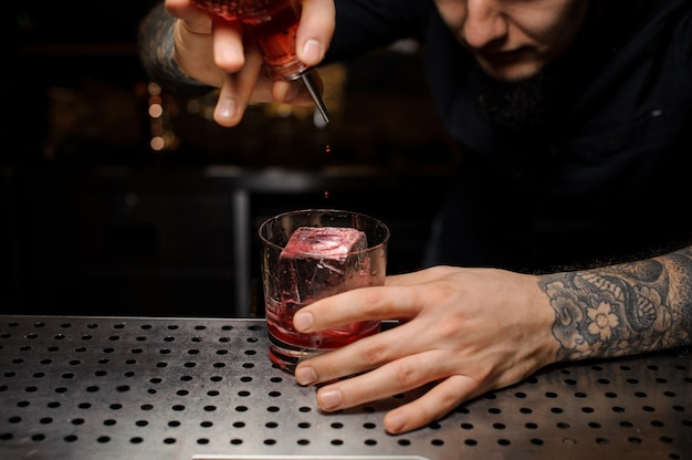 Bartender adding a bitter to the cocktail glass with ice cube from the special dasher bottle on the bar counter