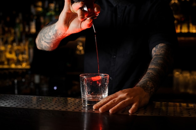 Bartender adding a bitter to the delicious cocktail from the special dasher bottle on the bar counter