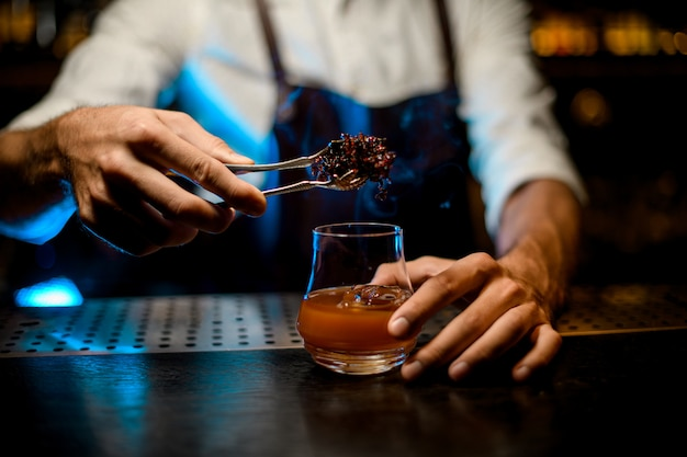 Bartender adding chilled melting caramel with twezzers to the cocktail glass with ice cubes under blue lights