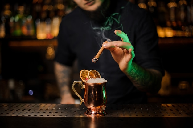 Bartender adding to a cocktail in the cooper glass with a dried orange aromatic smoked cinnamon on the bar counter