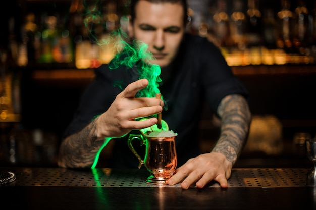 Bartender adding to a cocktail in the cooper glass with a dried orange aromatic smoked cinnamon in the green light on the bar counter