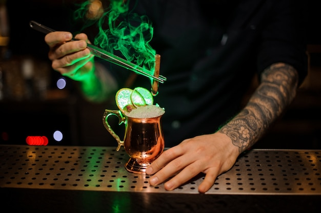 Bartender adding to a cocktail in the cooper glass with a dried orange aromatic smoked cinnamon with tweezers on the bar counter