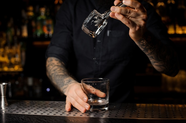 Bartender adding to a drink in the glass a big ice cube with tweezers on the bar counter