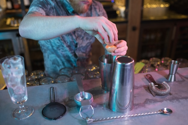 カウンターで飲み物を準備しながら卵黄を追加するバーテンダー