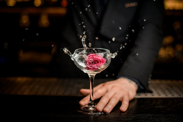 Bartender adding flower in an alcohol cocktail