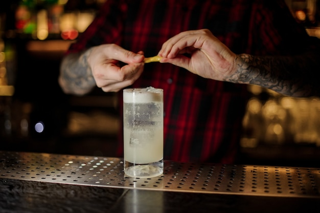Bartender adding orange zest juice to a gin fizz cocktail in the glass on the bar counter