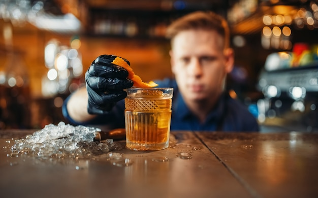 Бармен добавляет кожуру апельсина в алкогольный напиток