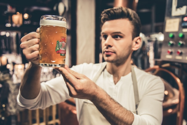 Bartender in apron is examining pitcher of beer.