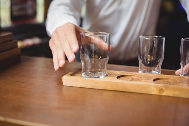 バーカウンターのトレイにビールグラスを配置するバーテンダー