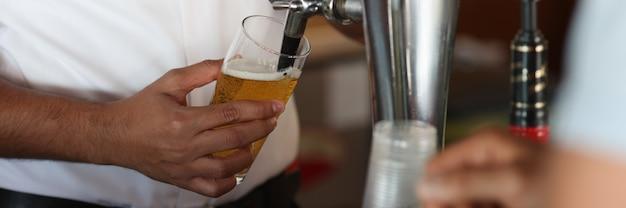 Бармен в баре наливает пиво в стакан