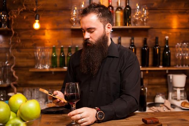 Бармен за прилавком наслаждается бокалом вина и разговаривает по телефону.