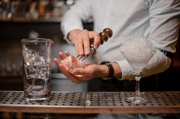Bartender breaking an ice cube for the cocktail