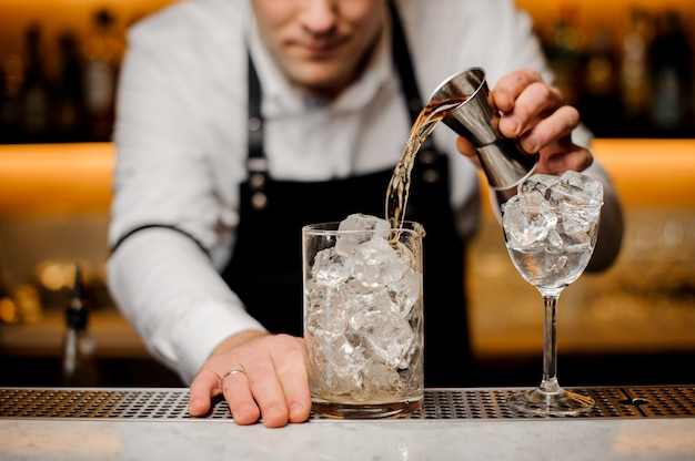 Bartender dressed in a white shirt pouring alcoholic drink into a glass with ice cubes