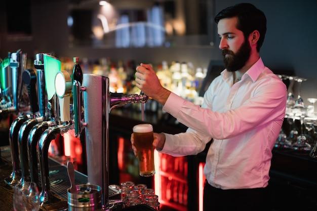 Бармен наливает пиво из барного насоса