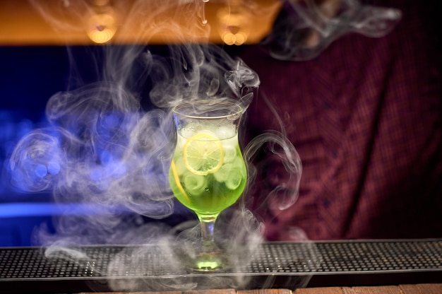 The bartender fills the prepared cocktail of lime and mint at the bar counter with smoke