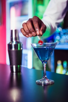 Bartender garnishing cocktail with cherry at bar counter in bar