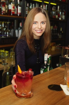 Bartender girl serving coctail to a customer